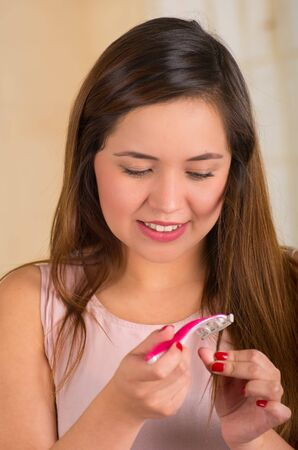 woman in bath: Beautiful young woman using a shaver on her hair, bath background Stock Photo