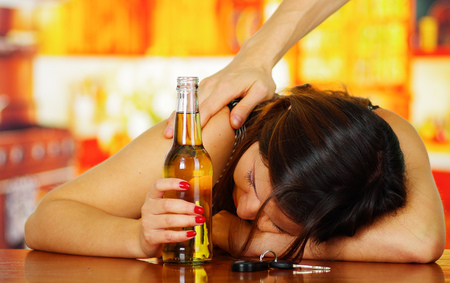 Portrait of a drunk woman sleeping over a wooden table and holding an open beer and car keys over the table, with a misterious hand in her shoulder, in bar background
