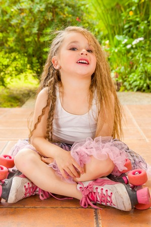 Little girl preschool sitting on ground wearing her roller skates and crossing her legs, in a garden background Stock Photo