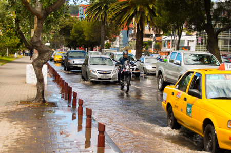 QUITO, ECUADOR - SEPTEMBER 20, 2016: A motocycle and car rides on a flooded road in Quito city after a heavy rain