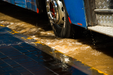 QUITO, ECUADOR - SEPTEMBER 20, 2016: Close up of a bus rides on a flooded road in Quito city after a heavy rain Editorial