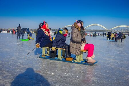 Harbin, China - February 9, 2017: Friends on a sled having fun on frozen river Songhua during winter time.
