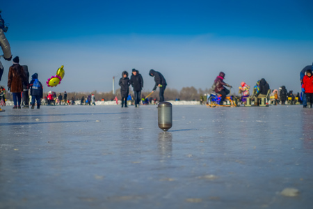Harbin, China - February 9, 2017: Spinning top on ice on frozen river Songhua during winter time.
