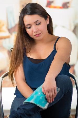 Beautiful female holding ice gel pack on leg, medical concept, in office background