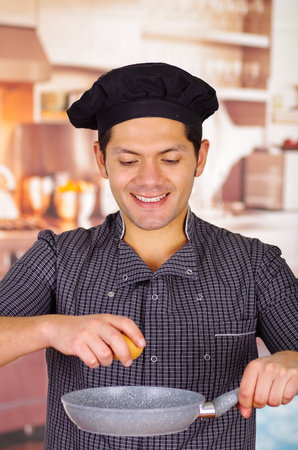 Smiling guy is holding a pan in kitchen with an egg in his hand cooking a dish, churrasco ecuatorian cuisine Banco de Imagens