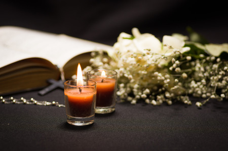 Two orange candles with a blurred rosary beads over a holy bible and small flowers, black background