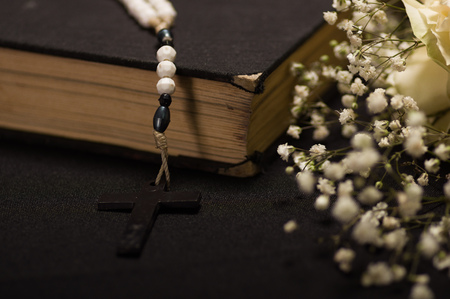 Close up of a rosary beads over a holy bible with blurred white small flowers, black background