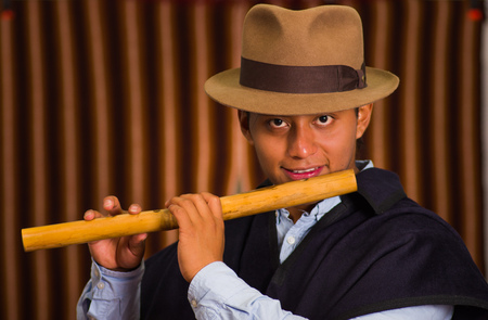 traje mexicano: Close up portrait of indigenous young man playing the quena flute