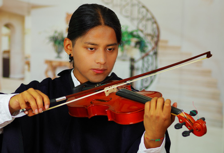 Indigenous young man from Otavalo, Ecuador, playing the violin