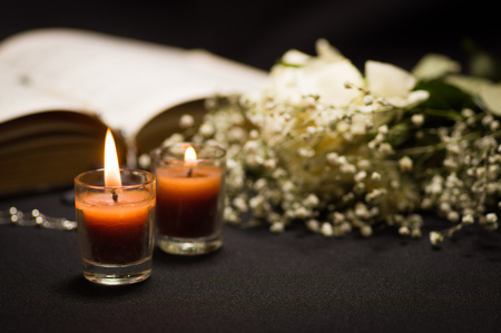 Close up of two orange candles with a blurred rosary beads over a holy bible and small flowers, black background Stock Photo
