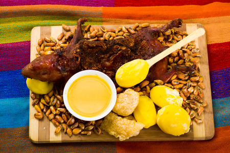 Traditional ecuadorian dish, grilled guinea pig spread out onto wooden board, tostados, bacon skin and lemons on the side, seen from above Stock Photo