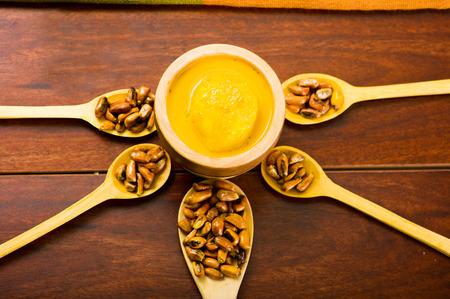 Cucharas de madera con granos de maíz tostado, conocido como tostado en América del Sur, se extendió alrededor de tazón que contiene salsa amarilla, visto desde arriba