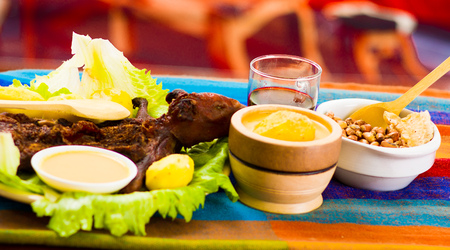 Traditional ecuadorian dish, grilled guinea pig spread out onto green plate, potatoes, tostados and lemons on the side, seen from above