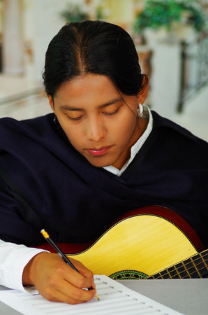 Indigenous young man writing notes to music with guitar, concept of composition