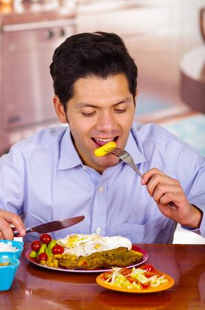 Man in kitchen eating a churrasco, ecuatorian cuisine