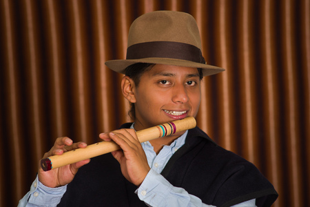 mexican ethnicity: Young man from Otavalo, Ecuador, playing the quena flute Stock Photo