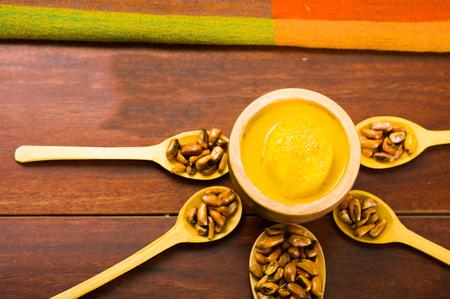 Cucharas de madera con granos de maíz tostado, conocido como tostado en América del Sur, se extendió alrededor de tazón que contiene salsa amarilla, visto desde arriba Foto de archivo