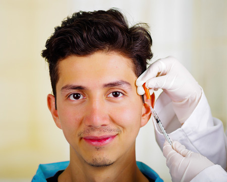 Handsome young man, receiving facial cosmetic treatment injections, doctors hand with glove holding syringe