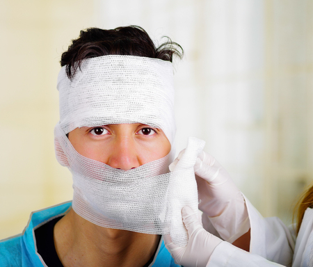 Doctor touching a men s head with trauma in his head and elastic bandaged around his head Stock Photo