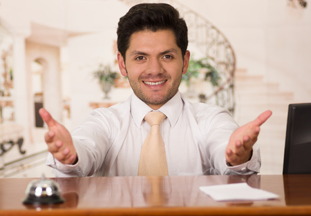 hotel staff: Happy smiling receptionist in hotel looking friendly for the guests