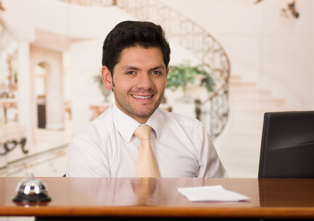 Happy smiling receptionist in hotel looking friendly for the guests