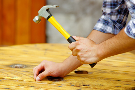 Casual man hammering nail in plank at home