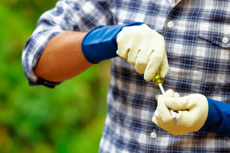 Attractive young builder holding a screwdriver wearing job gloves