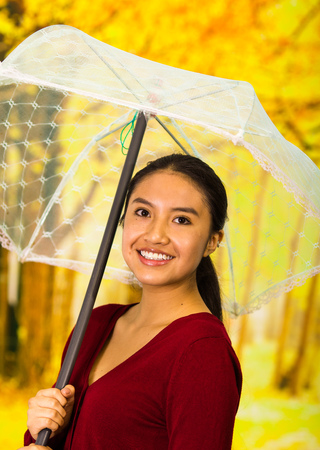 Young happy woman with umbrella wearing a red sweater at beautiful autum park