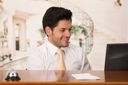 hotel staff: Happy smiling receptionist in hotel looking friendly for the guests in hotel background Stock Photo