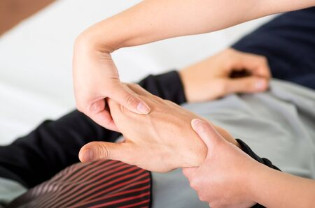 Close up of a massage physiotherapist doing hand massage of a male athlete, in medical office background