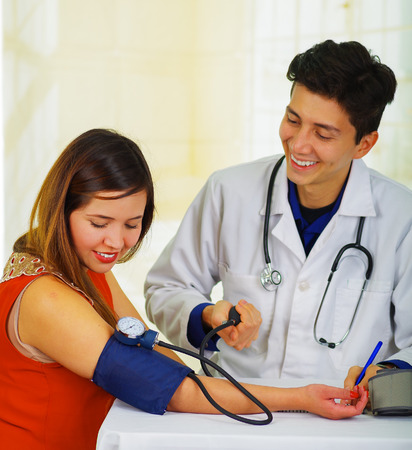 Close up of a handsome smiling young doctor with stethoscope around his neck taking the pulse to a young woman with a tensiometer, in a doctor consulting room background