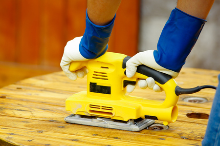 Close up of a man using an electric sander on pine floor or table sanding surface