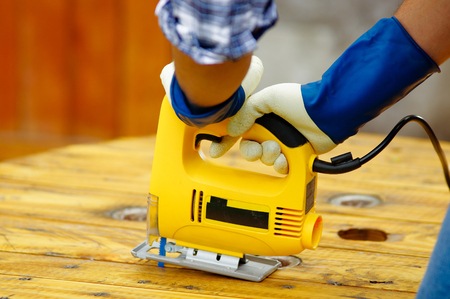 Close up of a man wearing job gloves working wood with electric jigsaw Stock Photo
