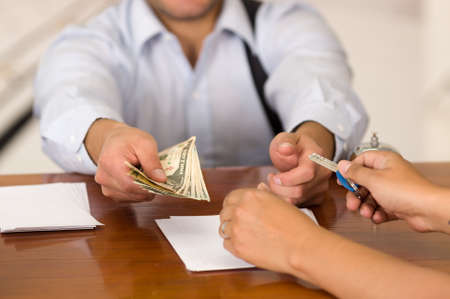 hotel staff: Guest pay the bill and receptionist in hotel giving key to guest