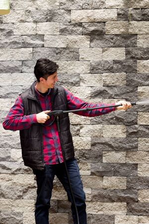 pressured: Handsome young man wearing square pattern red holding high pressure water gun, pointing towards grey brick wall