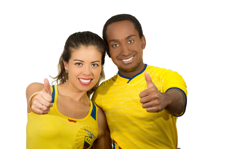 QUITO, ECUADOR - MAY 06, 2017: Young ecuadorian couple wearing official Marathon football shirt standing facing camera, with their thumbs up as a sign of victory, white background