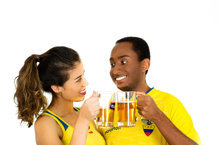 QUITO, ECUADOR - MAY 06, 2017: Young ecuadorian couple wearing official Marathon football shirt standing facing camera, sharing a glass of beer with his boyfriend, white background