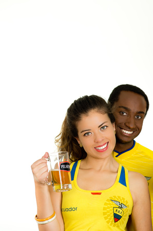 QUITO, ECUADOR - MAY 06, 2017: Close up of a young ecuadorian couple wearing official Marathon football shirt standing facing camera, and holding a glass of beer in white background Editorial
