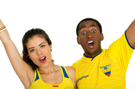 QUITO, ECUADOR - MAY 06, 2017: Close up of a young ecuadorian couple wearing official Marathon football shirt standing facing camera, screaming and shaking their arms of hapiness, white background