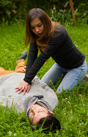 Beautiful woman giving first aid to a handsome young man, cardiopulmonary resuscitation, in a grass background