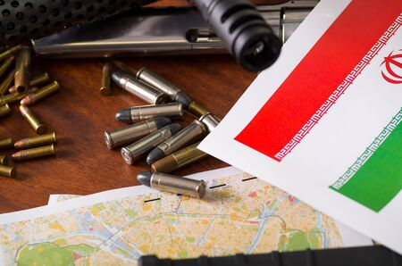 Close up of a shotgun and a revolver, cartridge belt with bullets with an Iran flag on a map, on wooden table