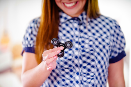 Young smiling woman holding a popular fidget spinner toy in her hand