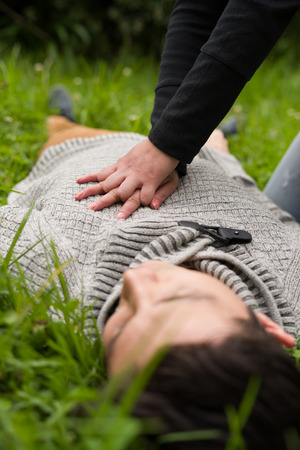 Close up of a beautiful woman giving first aid to a handsome young man, cardiopulmonary resuscitation, in a grass background Stock Photo
