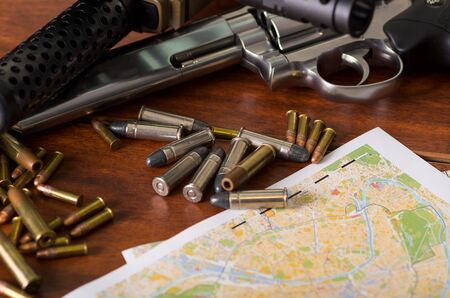 Bullets and a firearm. Bullets are a projectile expelled from the barrel of a firearm over a map, on wooden table