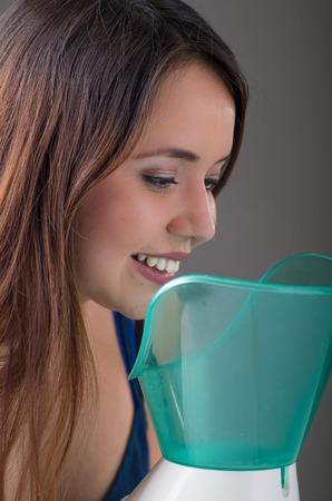 회색 배경에 기화기 nebulizer 기계와 흡입을하고 젊은 여자의 닫습니다 스톡 콘텐츠