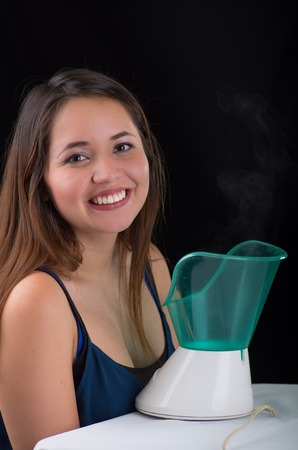 Young woman posing for camera behind of a medical vaporizer nebulizer machine on black background Banco de Imagens