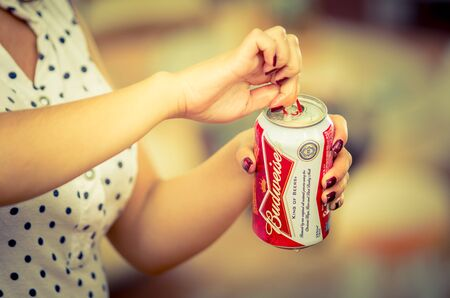 Quito, Ecuador - May 06, 2017: Young woman opening a refreshing Budweiser beer in a blurred background, vintage effect