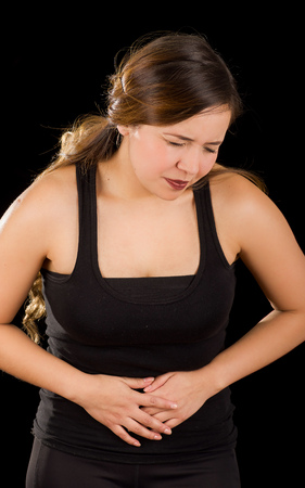 dolor: Beautiful young woman with stomach ache or nausea in a black background