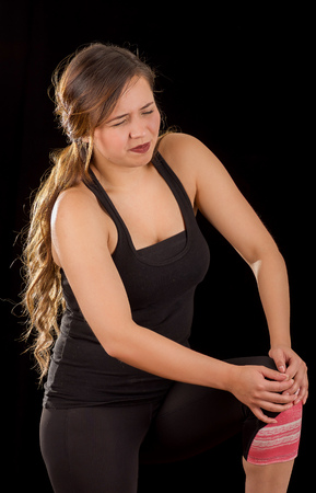 contracture: Beautiful young attractive sport woman holding injured knee suffering pain, in black background