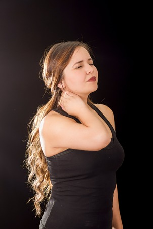 crick: Beautiful young lady Suffer crick after workout in a black background